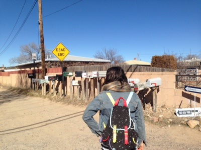Holly pausing in her footsteps to look at cluster dwelling in Santa Fe, New Mexico