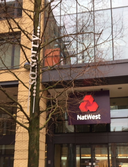 "words ""...so sorry"" installed in a tree outside a branch of the Nat West"